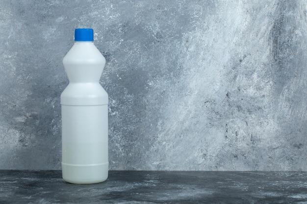 Witte container met bleekmiddel op marmer.