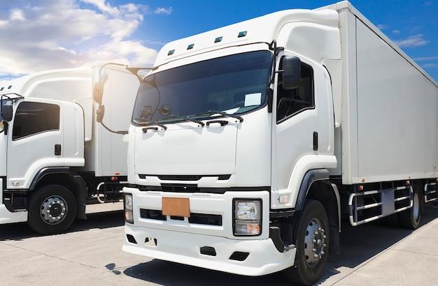 Witte containervrachtwagen op parkeren bij een blauwe hemel. vrachtvervoer.