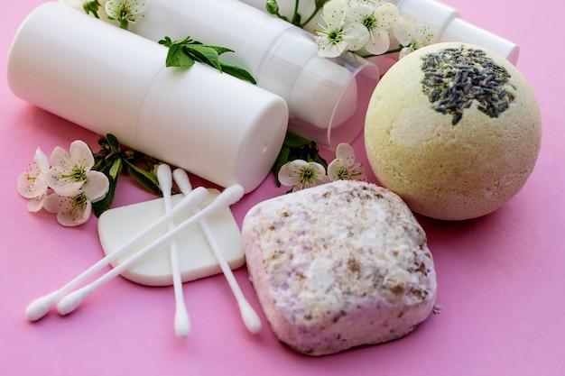 Witte cosmetische flessen, badbom, handgemaakte zeep, badzout, massageborstel, spons, wattenstaafjes met kersenbloemen op een roze achtergrond. natuurlijke biologische cosmetica concept.