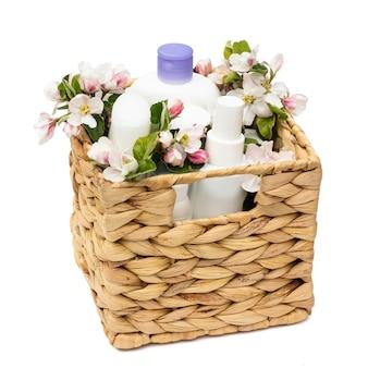 Witte cosmetische flessen in een rieten mand met perenbloemen geïsoleerd op een witte achtergrond. natuurlijke biologische cosmetica concept