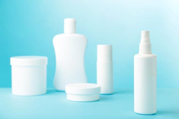 Witte cosmetische flessen op blauwe muur. bovenaanzicht