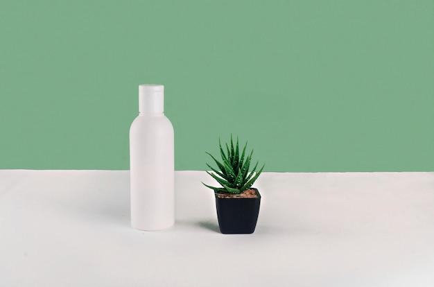 Witte cosmetische flessen op groene achtergrond met plaats voor tekst. huidverzorging, lichaams- of haarbehandeling.