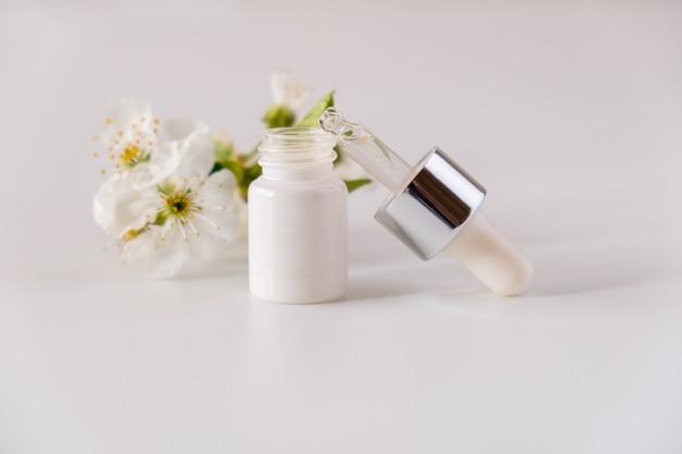 Witte cosmetische huidverzorging druppelflesje verpakking kersenbloesems bloemen op witte ondergrond