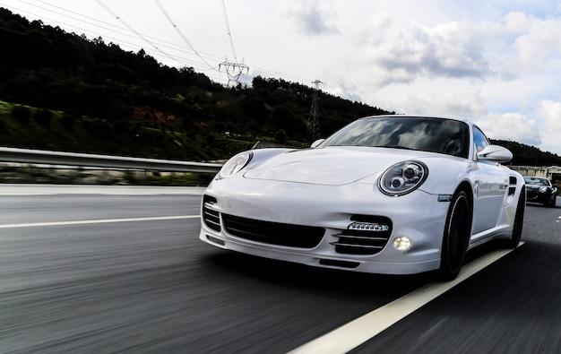 Witte coupé die op de weg rijdt.