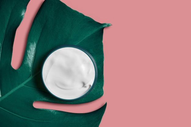 Witte crème in een pot op een exotische tropische blad op trendy roze. schoonheid en gezondheidszorgconcept. minimalistische plat lag met kopie ruimte.