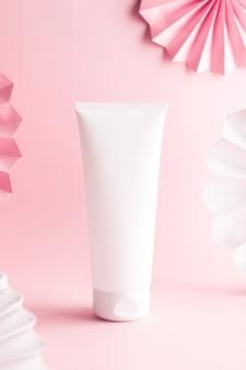 Witte crème tube op een roze achtergrond. versierd met papieren slinger, mock-up afbeelding