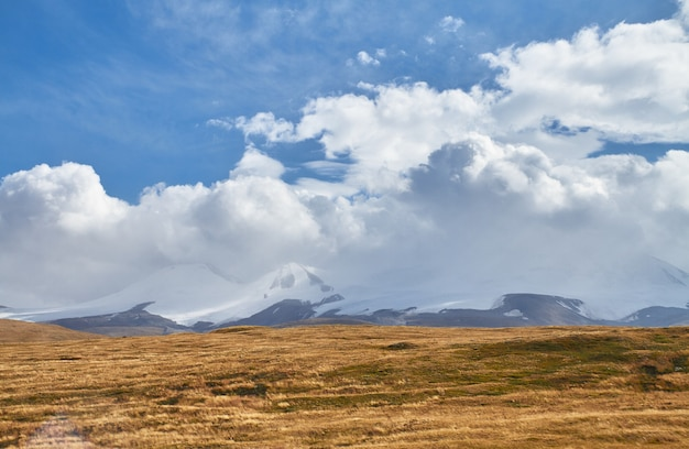 Witte cumulus-wolken komen uit de bergen, herfstlandschap in de steppe. het ukok-plateau in altai. fantastische koude landschappen. iedereen in de buurt