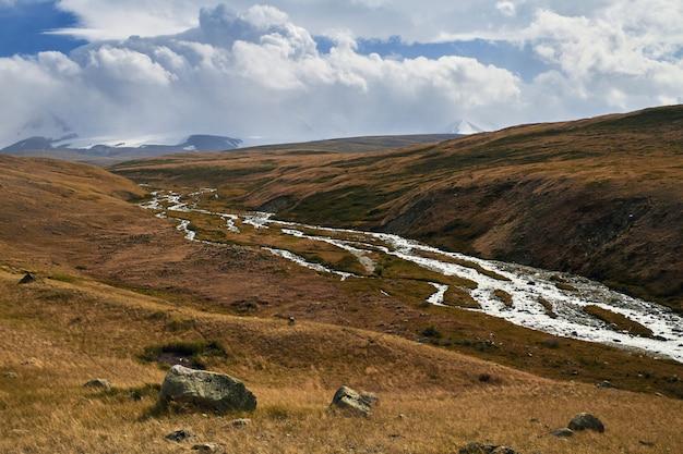 Witte cumuluswolken komen neer uit de bergen, herfstlandschap in de steppe. het ukok-plateau in altai