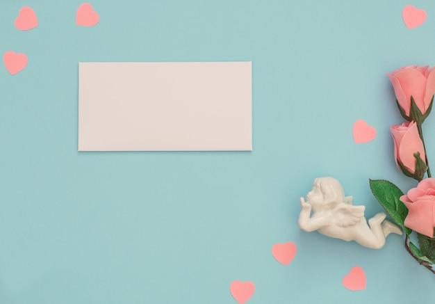 Witte cupido, envelop, roze roos op blauwe achtergrond