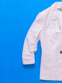 Witte damesjas. moderne modieuze dameskleding. plat leggen. het uitzicht vanaf de top.