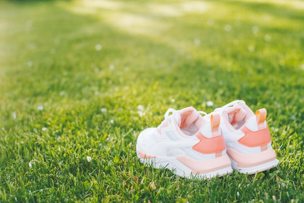 Witte damessneakers met koraal inzetstukken die op gras staan in zonnestralen. ruimte kopiëren