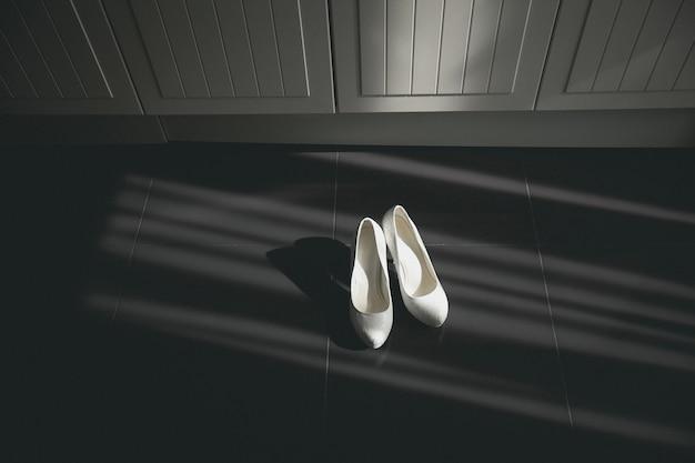 Witte de bruidschoenen van het ontwerperhuwelijk in stroken van zonlicht. nieuwe luxe moderne damesschoenen met lage hakken in gedessineerd leer, op zwarte of donkere vloer. ochtendvoorbereidingen voor de bruiloft.