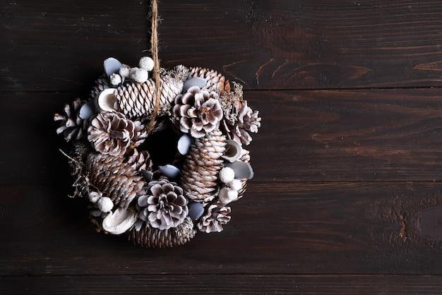 Witte de kroondecoratie van de kerstmisdeur die van pijnboom en sparappel op donkere houten wordt gemaakt, copyspace