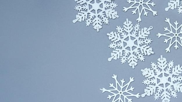 Witte decoratieve sneeuwvlokken op een grijze achtergrond. kerstmis en nieuwjaar, een plek voor tekst, minimalisme, winterachtergrond