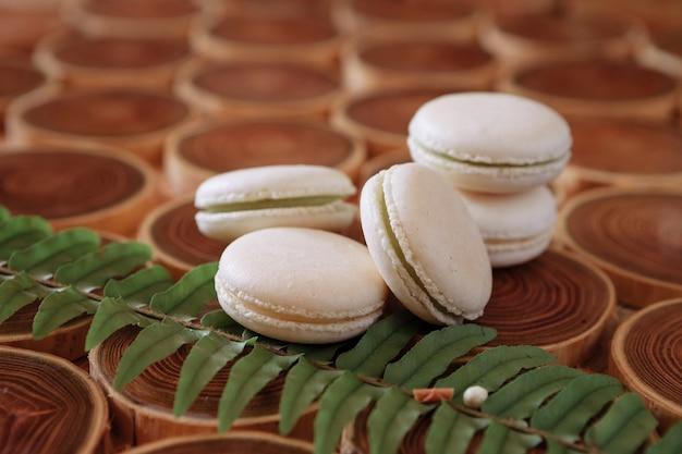 Witte delicate nederige bitterkoekjes op een houten achtergrond de pasteltint van de room in de franse koekjes