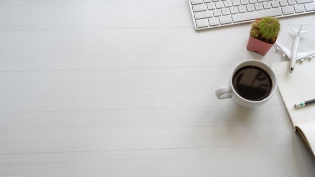 Witte designbureau-bureautafel met pc, verbruiksartikelen en kopieerruimte.