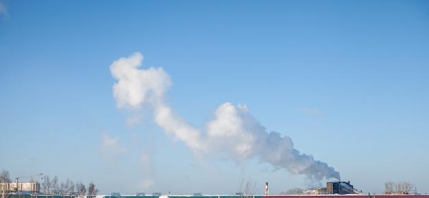 Witte dikke rook uit de schoorsteen van de stookruimte. rook tegen de blauwe lucht. luchtvervuiling. verwarming van de stad. industrie gebied.