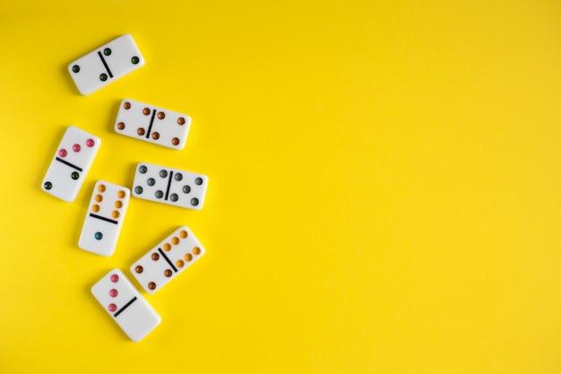 Witte dominostenen op gele achtergrond, bovenaanzicht. bordspel. plaats voor tekst