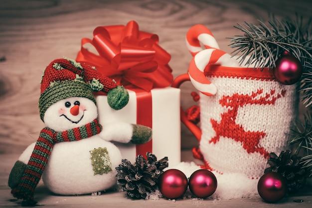 Witte doos met kerstcadeau, de kerstbeker en een speelgoedsneeuwman .foto met ruimte voor tekst