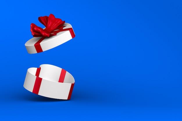 Witte doos met rode strik op blauwe achtergrond. geïsoleerde 3d-afbeelding