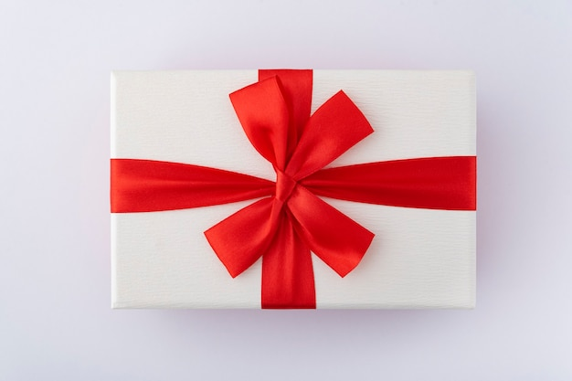 Witte doos met rood lint en boog op witte achtergrond. bovenaanzicht.