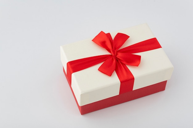 Witte doos met rood lint op witte achtergrond. cadeaupapier.