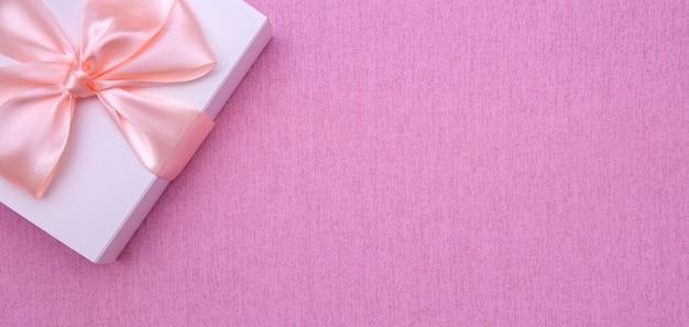 Witte doos met strik op roze achtergrond