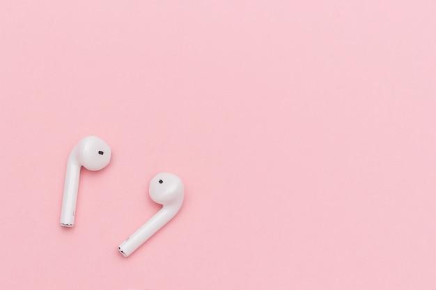 Witte draadloze bluetooth-hoofdtelefoons op roze document achtergrond. sjabloon voor tekst of uw ontwerp.