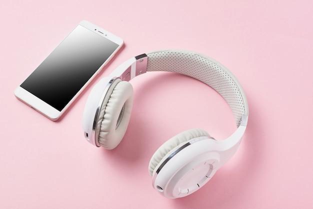 Witte draadloze hoofdtelefoons en smartphone op pastelroze
