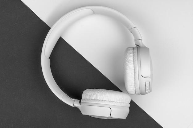 Witte draadloze hoofdtelefoons liggen op een zwart-witte achtergrond