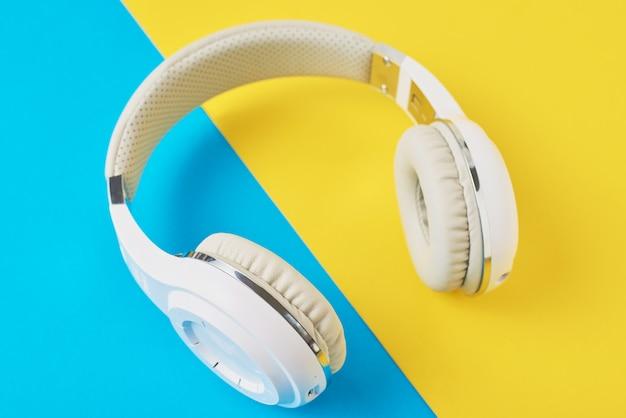 Witte draadloze hoofdtelefoons op een blauwe en gele achtergrond