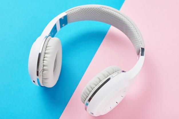 Witte draadloze hoofdtelefoons op een pastel roze en blauwe achtergrond