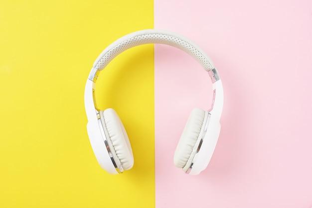 Witte draadloze hoofdtelefoons op een roze en gele achtergrond