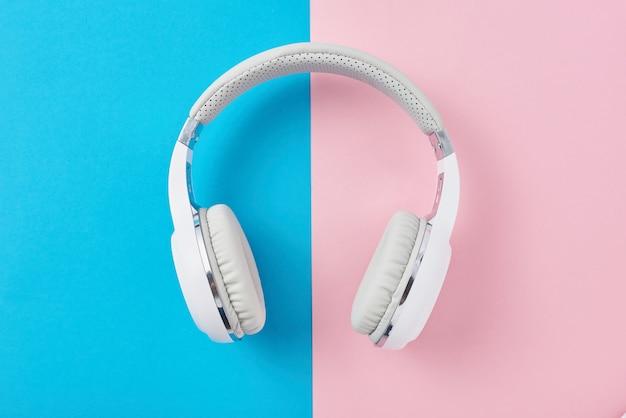 Witte draadloze koptelefoon op pastelroze en blauw