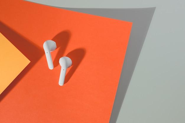 Witte draadloze koptelefoons liggen op een gekleurde achtergrond