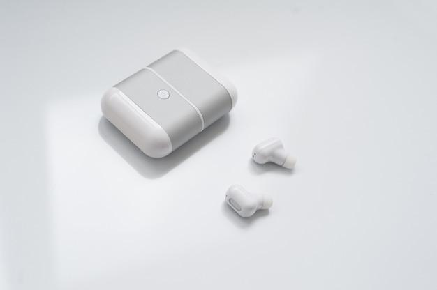 Witte draadloze oortelefoons met het laden van geval dat op witte achtergrond wordt geïsoleerd.