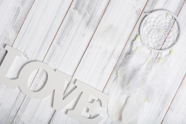 Witte dromenvanger en liefde tekst op houten tafel, plat lag