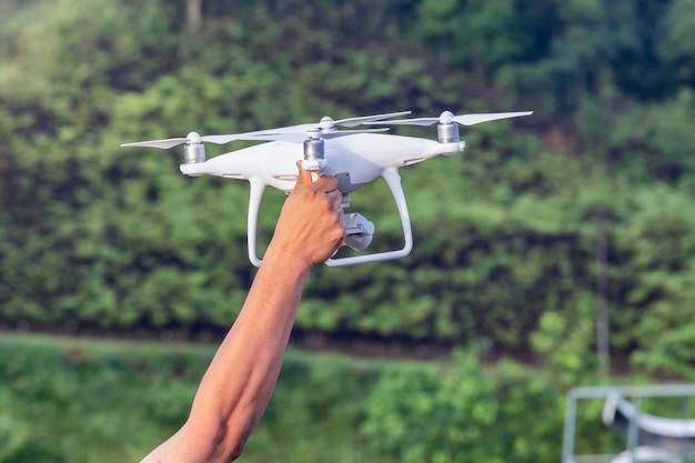 Witte drone die in een ochtend met hand hangt