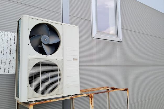 Witte dubbele buitenunit van airconditioner op grijze muur van winkelcentrum. een van de ventilatoren zonder beschermrooster, mogelijk kapot.
