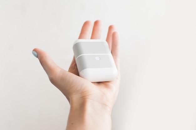 Witte echte draadloze oortelefoons met het laden van geval dat op witte achtergrond wordt geïsoleerd