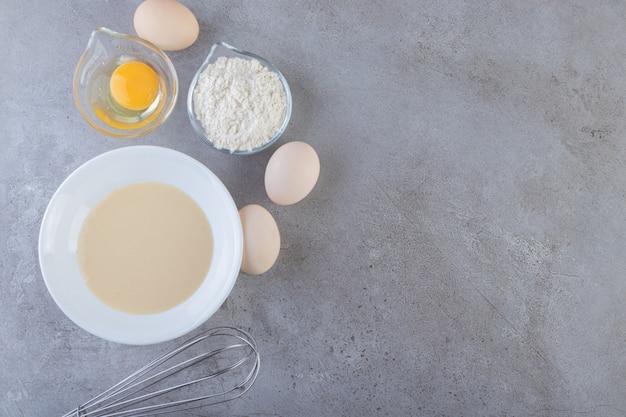 Witte eieren, dooier en kom met bloem op stenen tafel.