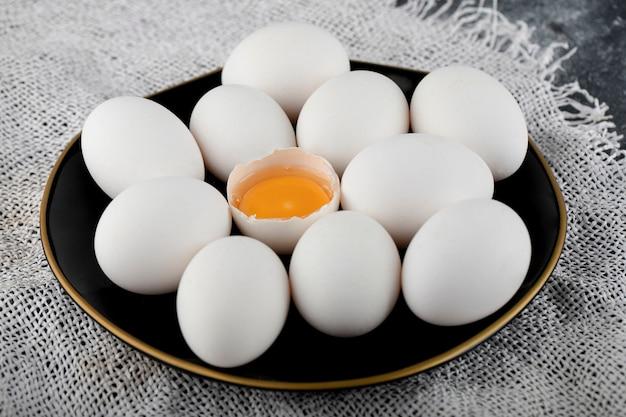 Witte eieren en dooier op zwarte plaat.
