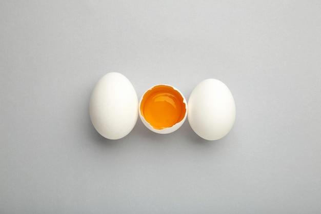 Witte eieren en eigeel op de grijze achtergrond.