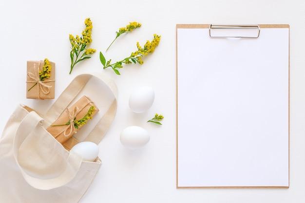 Witte eieren, gele bloemen, ambachtelijke geschenken vliegen uit een stoffen zak en een klembord met papier op wit