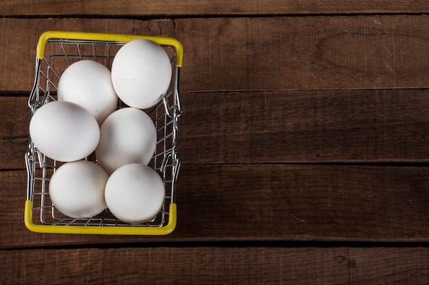 Witte eieren in een ijzeren voedselmand op een houten tafel, bovenaanzicht, met een kopie van de ruimte.