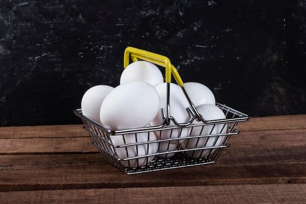 Witte eieren in een ijzeren voedselmand op een houten tafel.