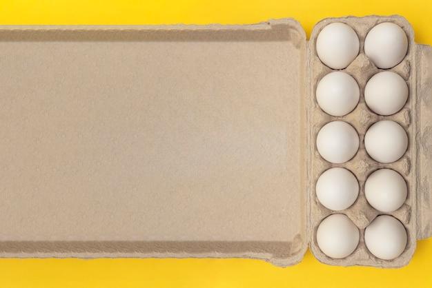 Witte eieren in een kartonnen doos op een gele achtergrond