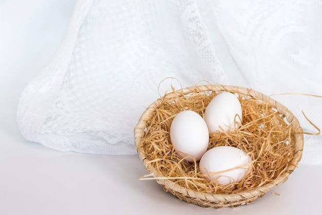 Witte eieren in een mand in een wit zacht licht.