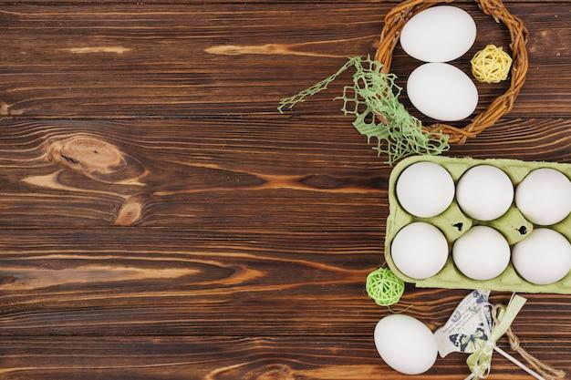 Witte eieren in rek met kleine vogel en houten ballen op tafel