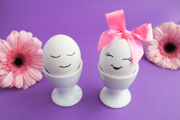 Witte eieren in witte onderzetters en bloemen